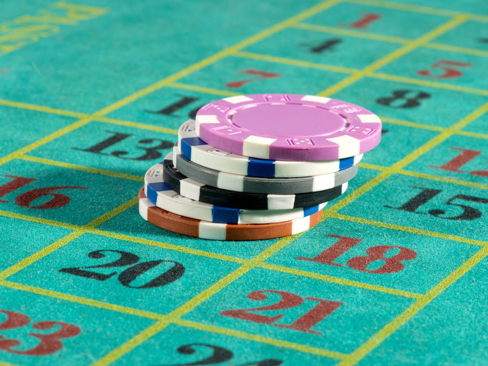 Gambling chips on roulette table in casino