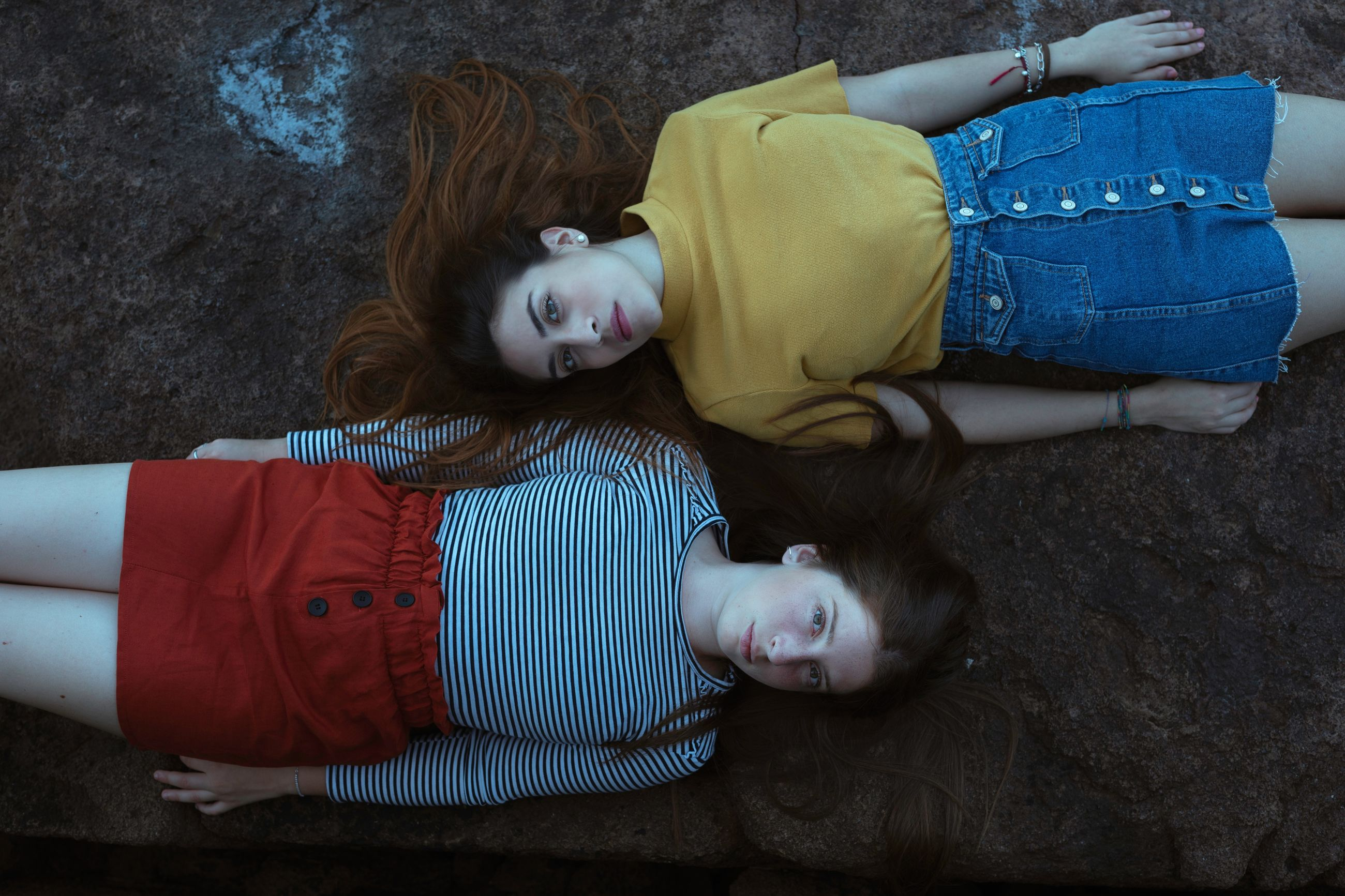 HIGH ANGLE PORTRAIT OF CUTE GIRL LYING DOWN ON SOFA