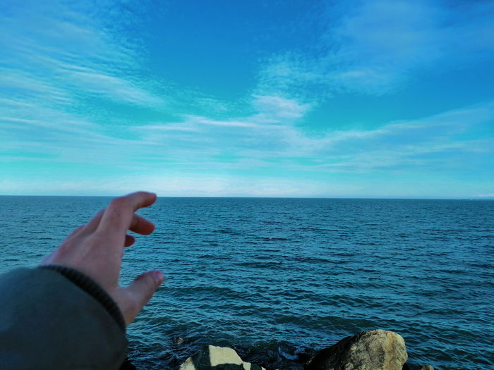 Midsection of person on sea against sky