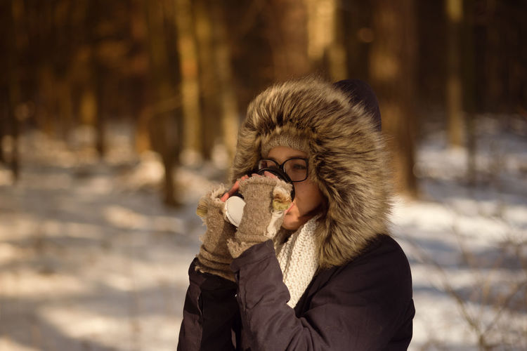 Close-Up Of Woman Drinking Coffee While Wearing Winter Coat