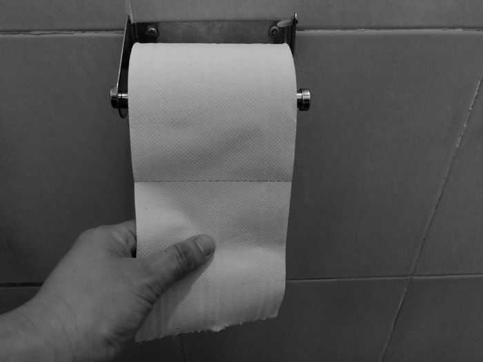 Cropped hand of man holding toilet paper in bathroom
