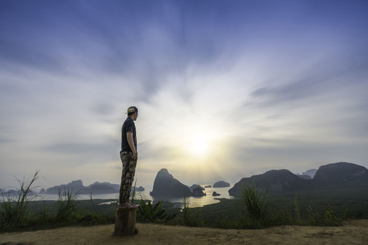 Man standing on land against sky during sunset
