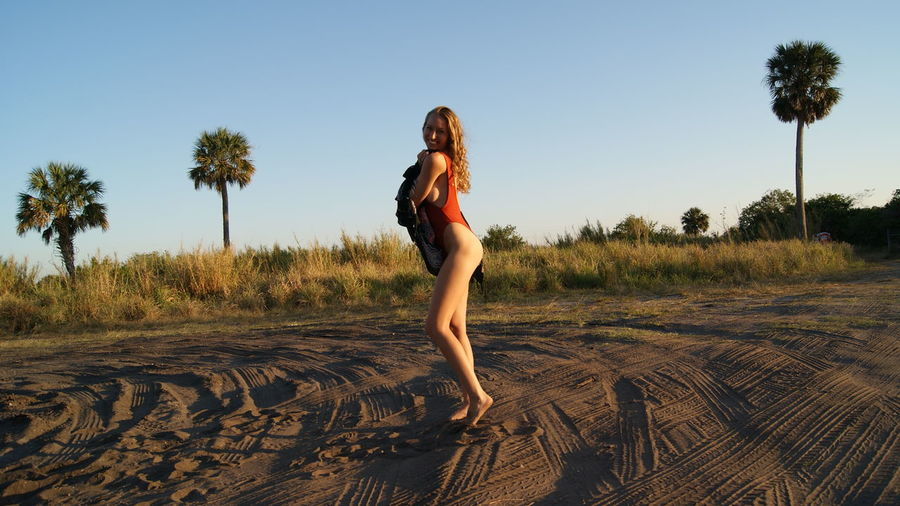 Side view full length of young woman wearing one piece swimsuit standing on sand