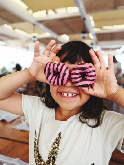 Portrait of cute smiling girl covering face donuts