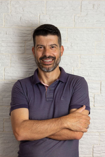 Portrait of smiling man standing against wall