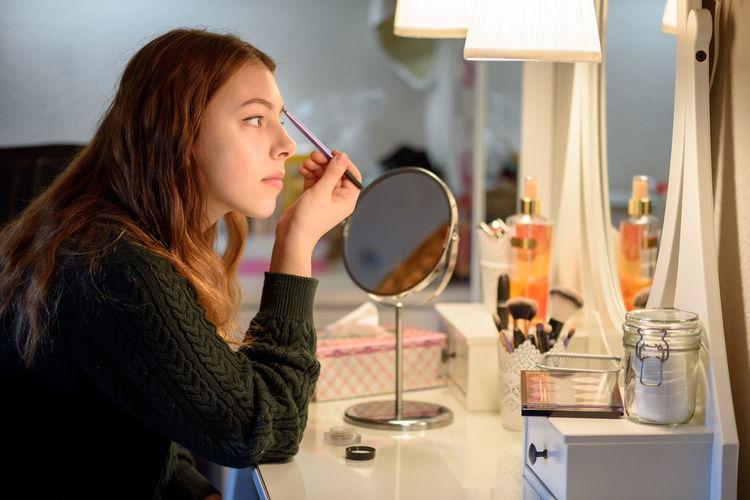 Young woman applying make-up on table