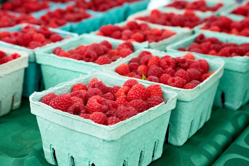 Fresh raspberries for sale on market stall