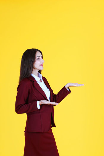 Side view of a young woman against yellow background