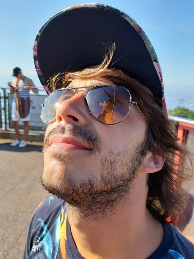 Man wearing sunglasses and cap against sky