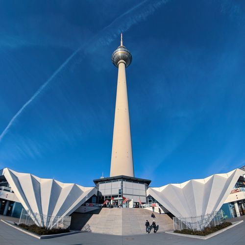 Low angle view of berliner fernsehturm against blue sky in city