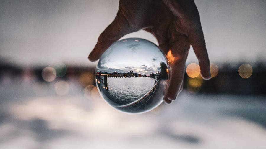Holding a glassball hands, seeing berlin through the lens upside down