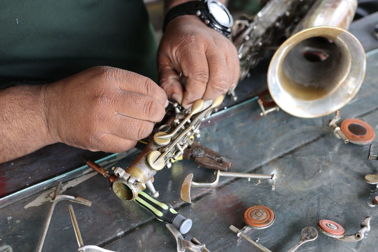 Midsection of man repairing musical instrument in workshop