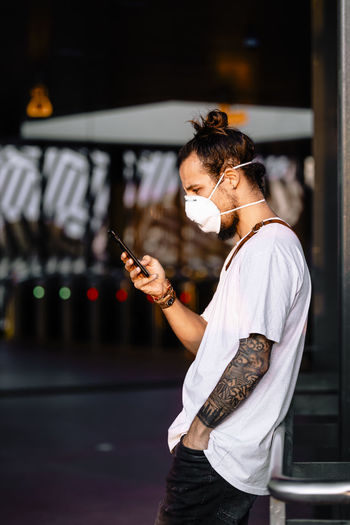 Side view of man wearing mask using mobile phone while standing outdoors