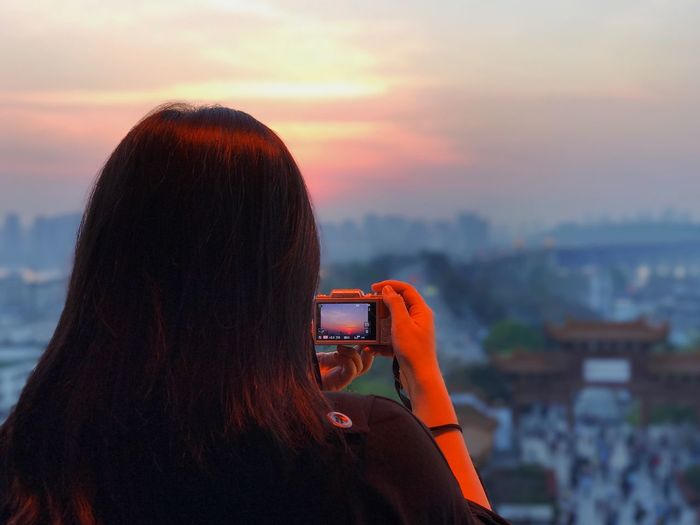 Rear View Of Woman Photographing Cityscape Against Sky During Sunset