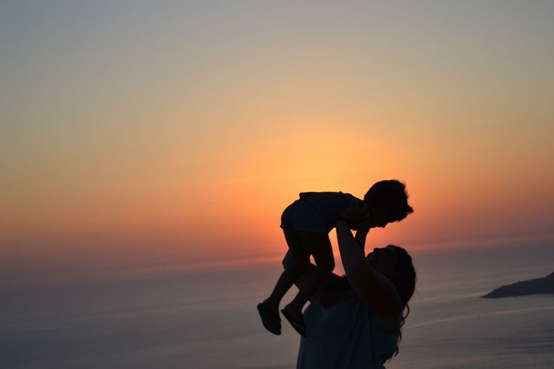 Silhouette Of Mother With Child At Beach