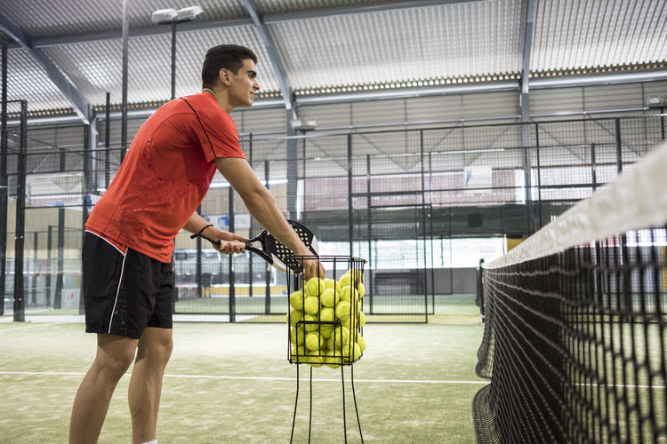 Man holding racket while playing paddle tennis