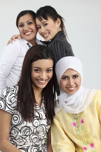 Portrait of smiling female friends standing against white background