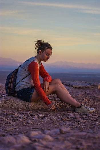 Side view of woman sitting rock against sky during sunset
