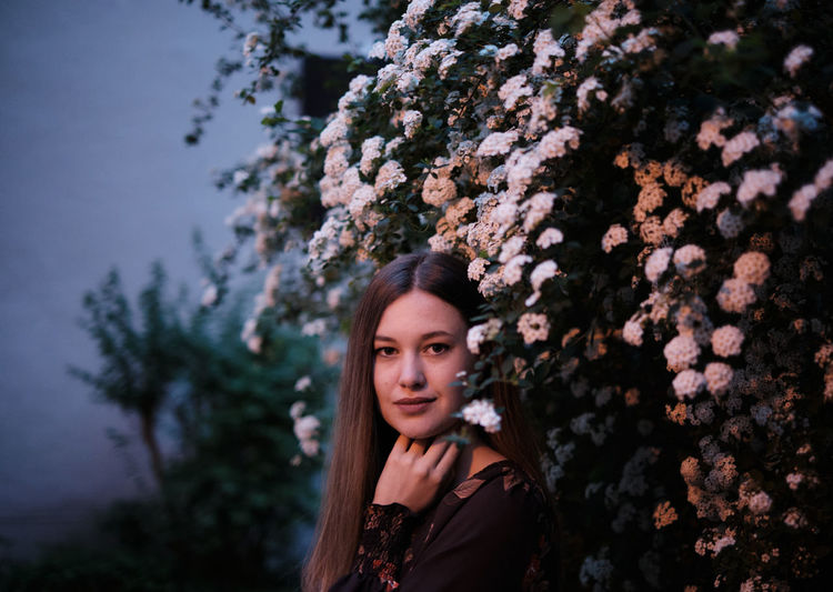 Portrait of young woman standing by plants in park at night