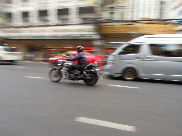 People riding motorcycle on street in city