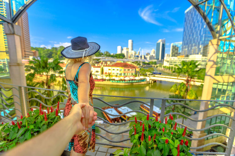 Follow me. Tourist woman with wide hat holding hand of partner looking panorama from terrace over Clarke Quay and Riverside area in Singapore, Southeast Asia. Lady enjoys on Singapore River downtown. Singapore Singapore City Woman Tourist Tourist Attraction  Tourist Destination People Girl Females Aerial View Skyline Cityscape Panorama Happy Travel Hat Lifestyle Enjoy Nature Tourism Follow Me Hand In Hand River Clarke Quay Clarke Quay, Singapore Boats Cruise Building Exterior One Person Architecture Built Structure City Real People Lifestyles Adult Leisure Activity Plant Water Sky Day Women Clothing Holding Hand Outdoors Office Building Exterior