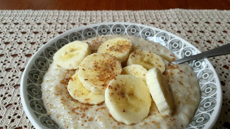 Close-up of porridge with sliced bananas in bowl at home