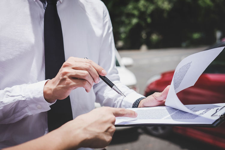 Midsection of customer pointing at contract while insurance agent holding clipboard