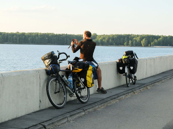 Adventure By Bike Adventure Bicycle Bike Packing Bike Touring Casual Clothing Cyclo Travel Day Full Length Lake Land Vehicle Leisure Activity Lifestyles Mode Of Transport Nature One Person Outdoors People Real People Rear View Sitting Sky Transportation Tree Water Young Adult