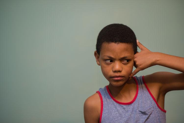 Boy Gesturing Against Wall