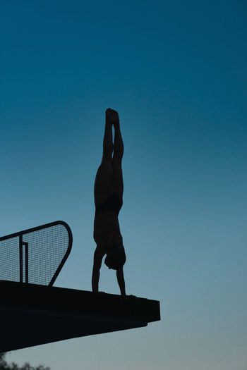 Silhouette Of Diver In Handstand, Preparing To Dive From Platform. Photographed At Dusk Swimming Diving Aquatics Athlete Dark Diving Platform Handstand  Individual Sports Silhouette Summer Olympic Games Water Sport Woman Blue Dive Female Muscular Build One Person Outdoors Pool Sport Strength Swimming Pool Water Young Adult Young Women