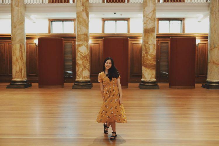 Portrait of smiling woman standing on hardwood floor