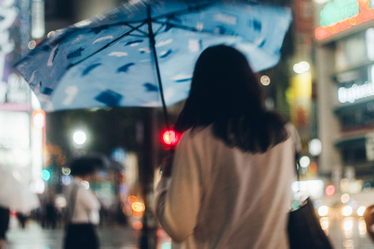 Rear View Of Woman With Umbrella Walking At Night