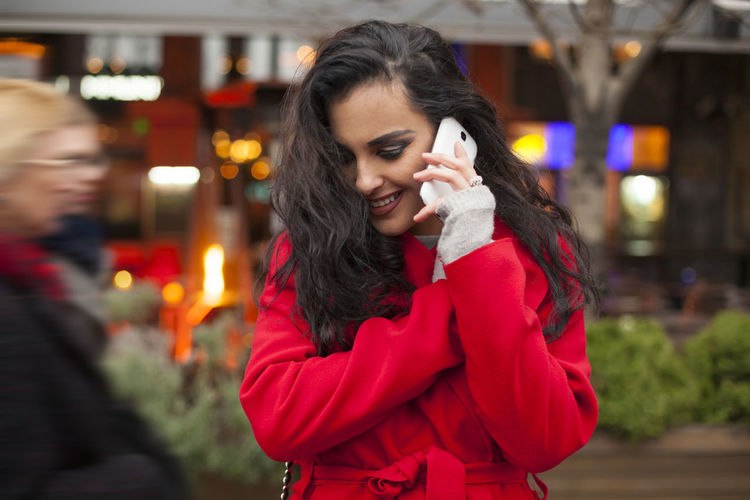 Smiling young woman talking on mobile phone while standing on city street