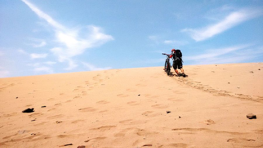 Rear view of traveler with bicycle walking on sand dune against sky