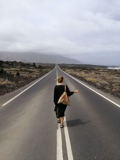Rear view of woman hitchhiking on road against sky