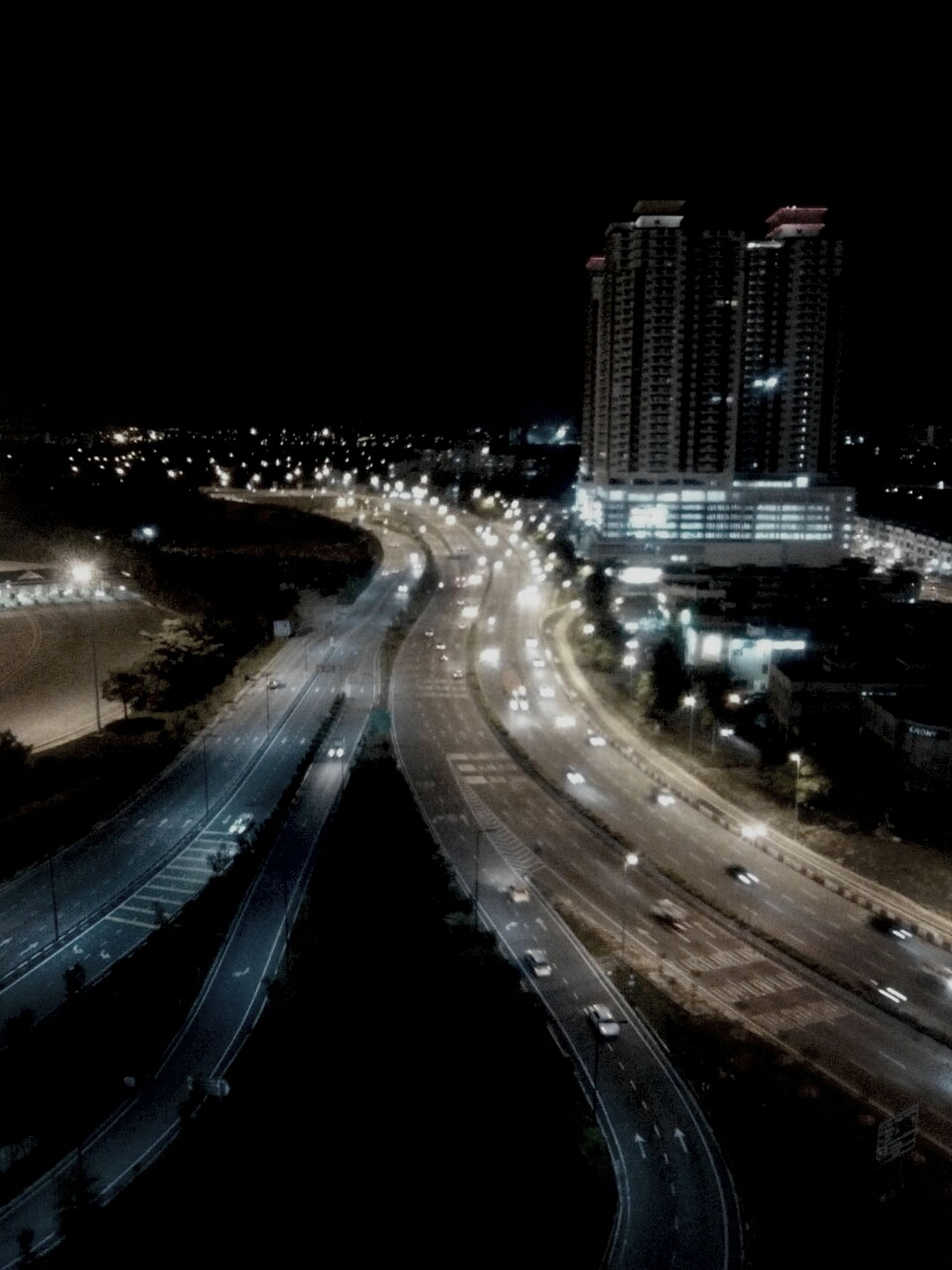 night, illuminated, city, building exterior, architecture, built structure, transportation, road, high angle view, street, cityscape, long exposure, street light, city life, motion, light trail, car, skyscraper, city street, traffic