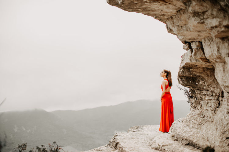 Woman standing on rock against clear sky