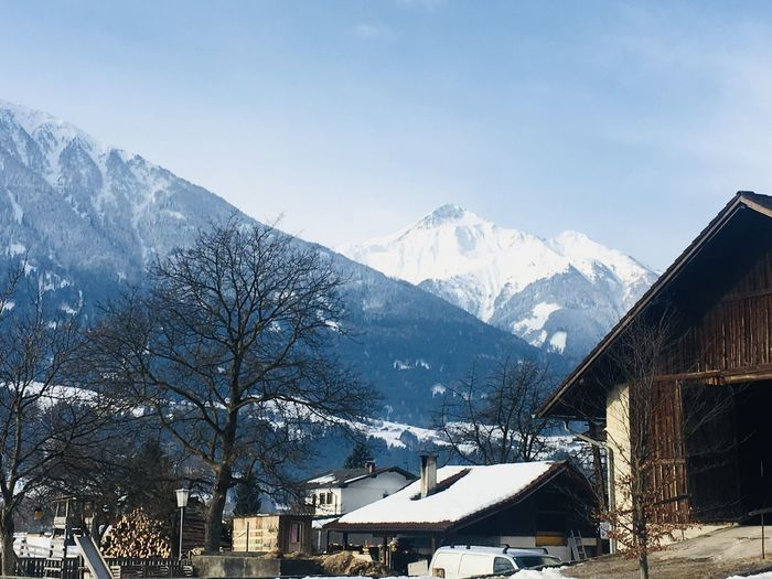 Houses and snowcapped mountains against sky