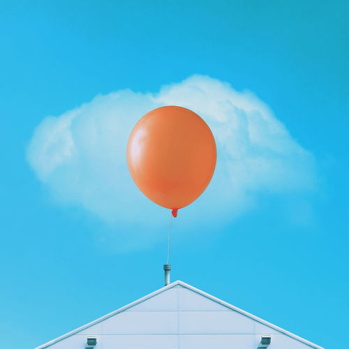 Low angle view of balloons against blue sky