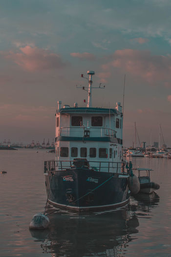 Fishing boats in harbor at sunset