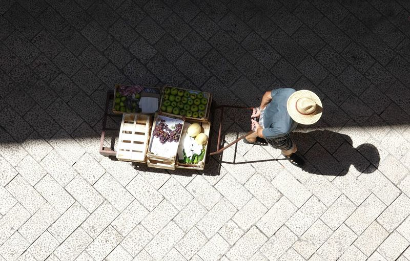 High angle view of man pulling a cart on street