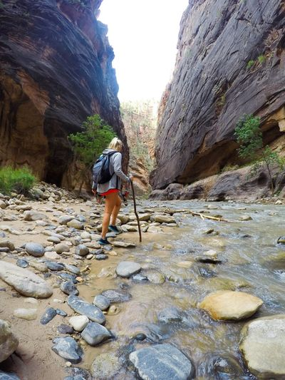 Hiker Walking On Stream Amidst Rock Formation