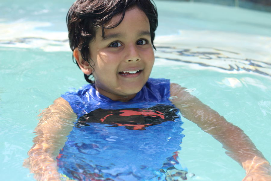 Boys Childhood Close-up Day Elementary Age Happiness Headshot High Angle View Leisure Activity Lifestyles Looking At Camera Mouth Open One Person Outdoors Portrait Real People Smiling Sunlight Swimming Swimming Pool Vacations Water Wet