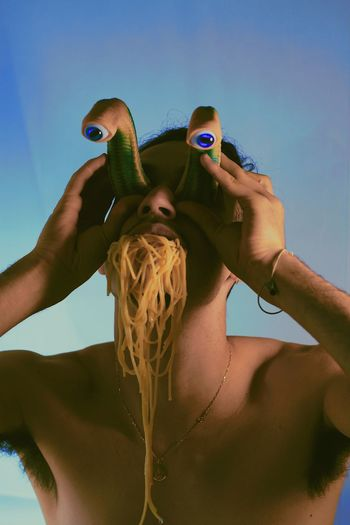 Low angle view of man holding artificial eyes while noodles in mouth against sky