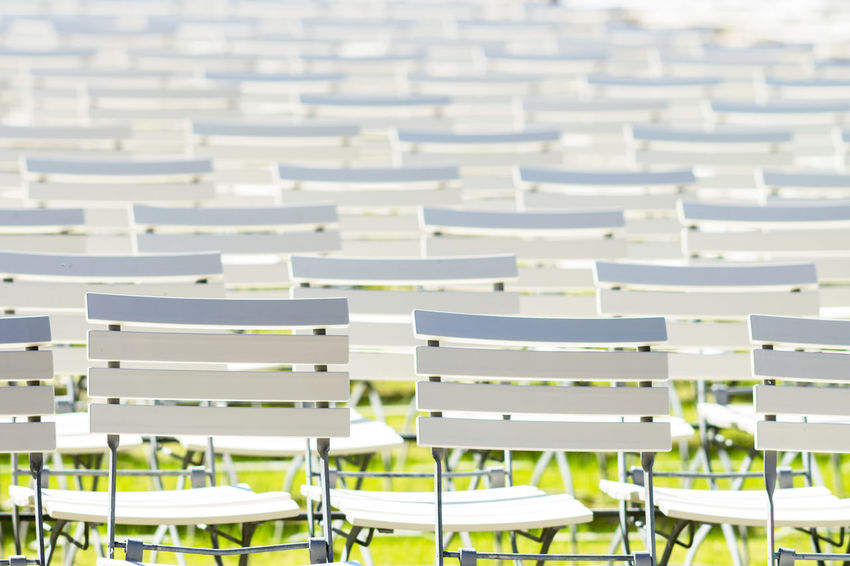 White chair rows in a spa park Backgrounds Bleachers Chair Chairs Chairs Seats Day Empty Focus On Foreground In A Row Large Group Of Objects No People Park Seat White Color