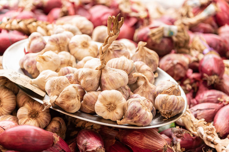 Close-up of garlic and onions for sale in market