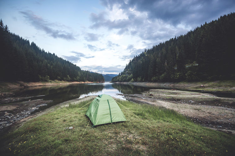 Wilderness tent camping against blue cloudy sky on sunrise Camping Cloudy Sky Beauty In Nature Cloud - Sky Day Forest Grass Green Color Lake Land Mountain Nature No People Non-urban Scene Outdoors Plant Scenics - Nature Sky Sunrise Tent Tranquil Scene Tranquility Tree Water Wilderness
