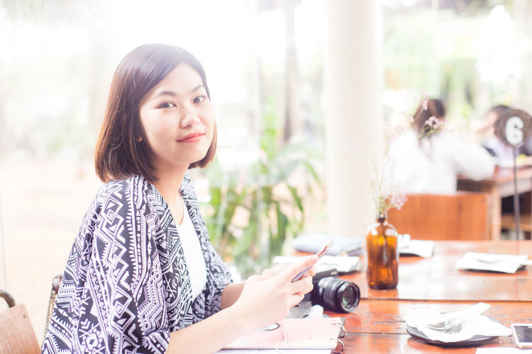 Portrait Of Woman Using Mobile Phone On Table