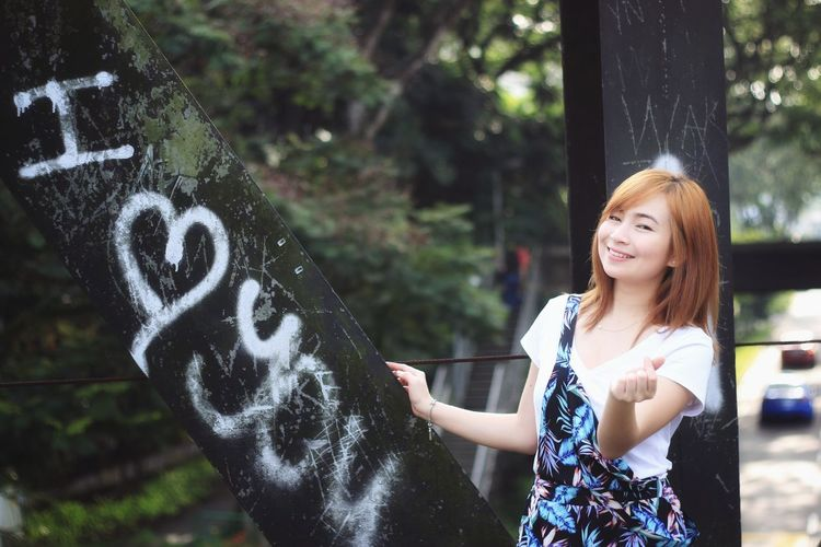 Portrait of smiling young woman standing by i love you text