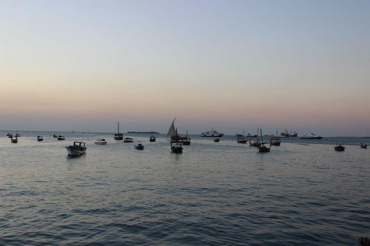 Boats anchored on sea at dusk